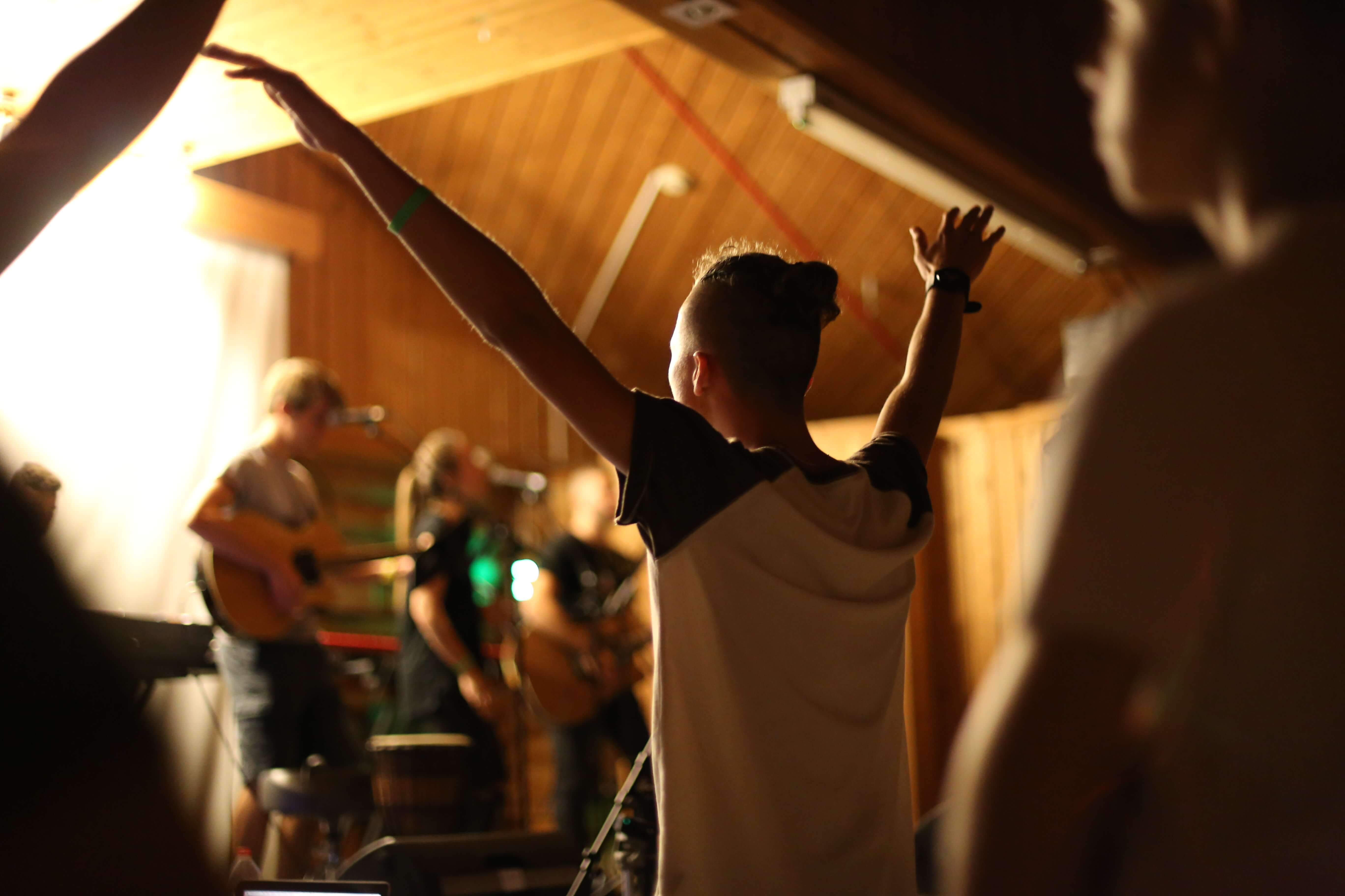 A teen lifting hands in praise ... a background of worship musicians playing guitars and singing