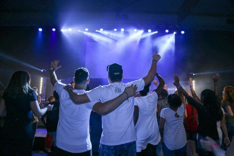 Teenagers worshiping with their hands raised in praise while they observe a music concert